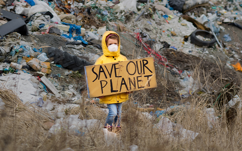 A child in a rubbish dump in a yellow anorak & face mask with 'Save the Planet' placard showing worry around face mask waste
