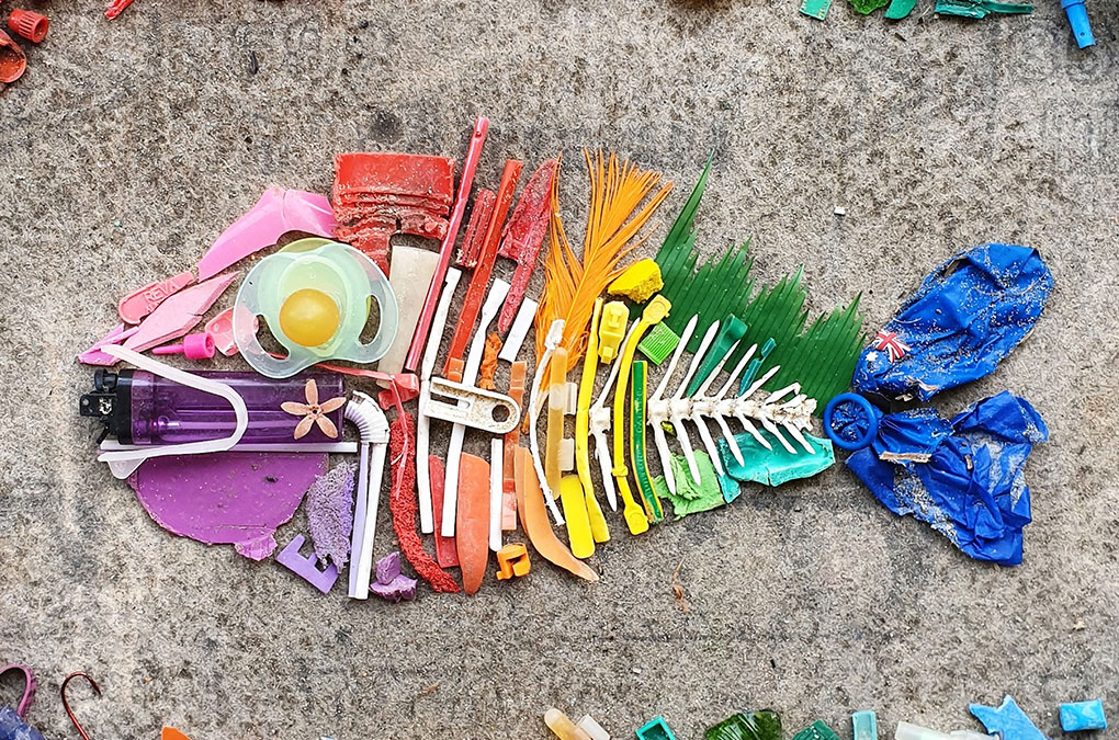 A rainbow-coloured fish made up of different individual waste items, showing why plastic-free is the way to be - a green guide